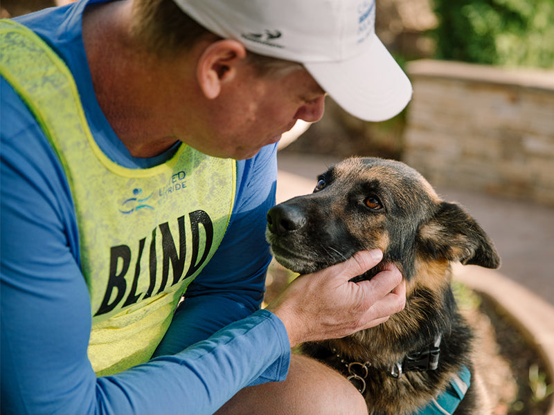 Man in yellow bib that reads blind with German shepherd guide dog sharing a moment.