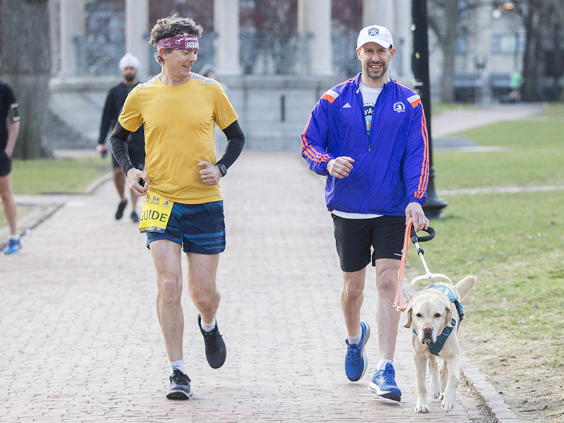 Blind runner in running race with human and dog guide at his side.