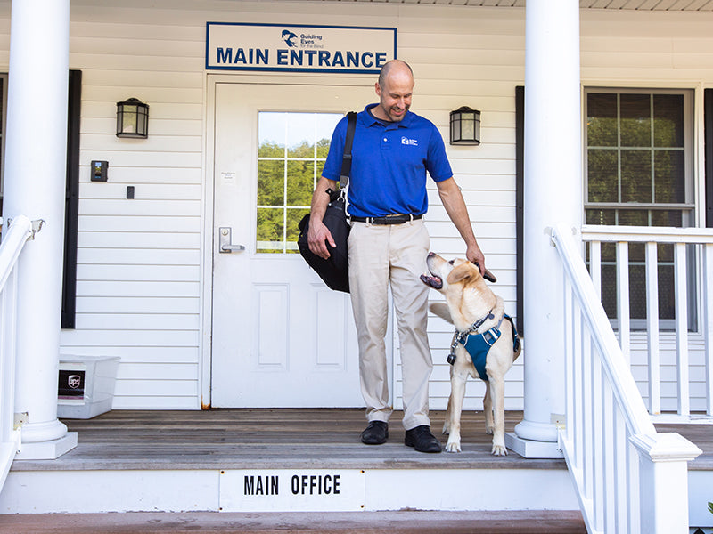 Human and dog in Unifly harness stand on porch of guiding eyes for the blind.