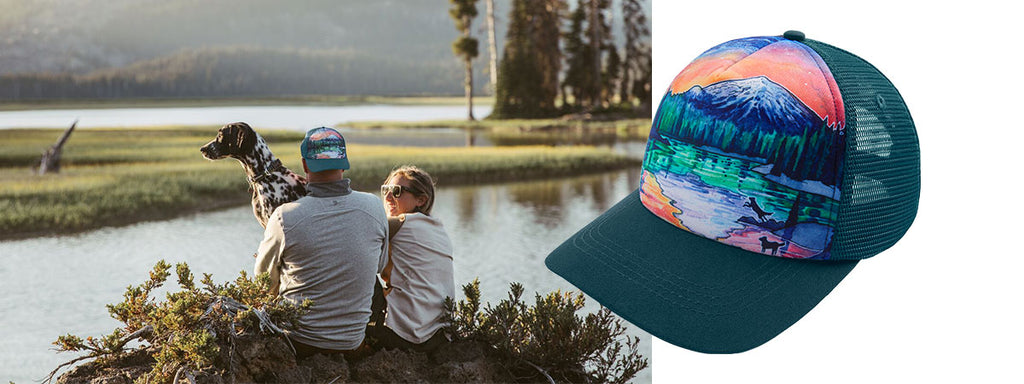 Brian wears artist series hat while sitting with Dani and pup Vilas lakeside at Sparks Lake.