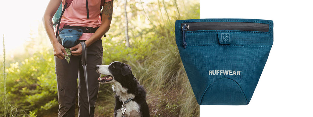 Woman grabs pick up bags out of the pack out bag on her hip while dog sits on trail at her side.