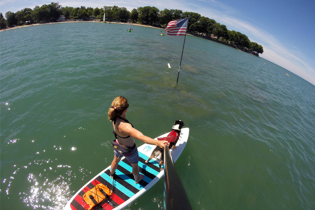 Maria and Kona paddling out to the American Flag in Lake Erie on the Fourth of July.