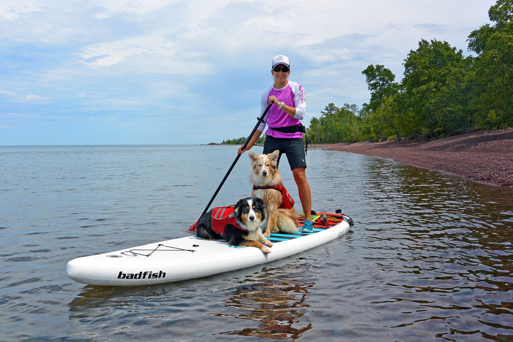 Maria, Riley and Kona paddling together along the red-pebbled beaches of Lake Superior.