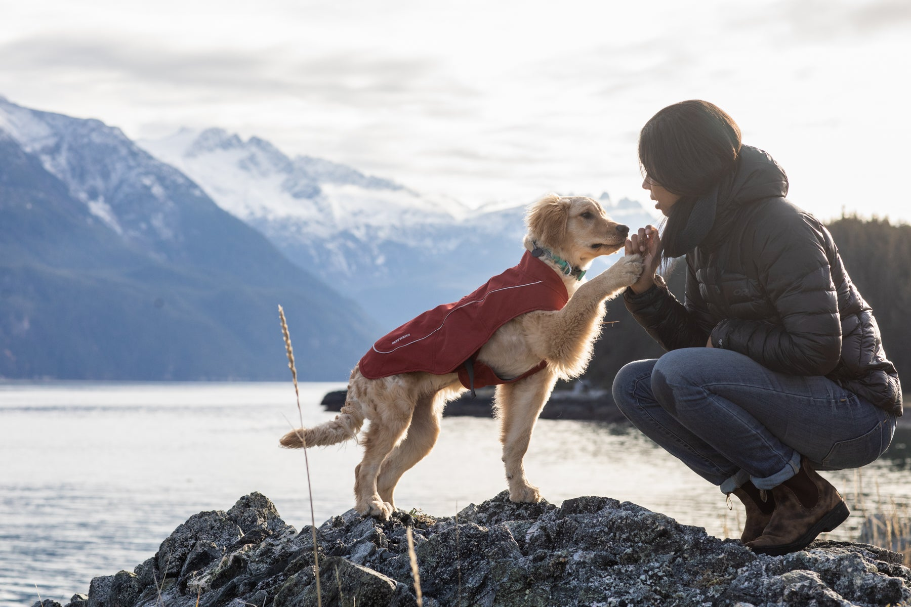 Sammy in Overcoat jacket gives Chris a high five by the river.