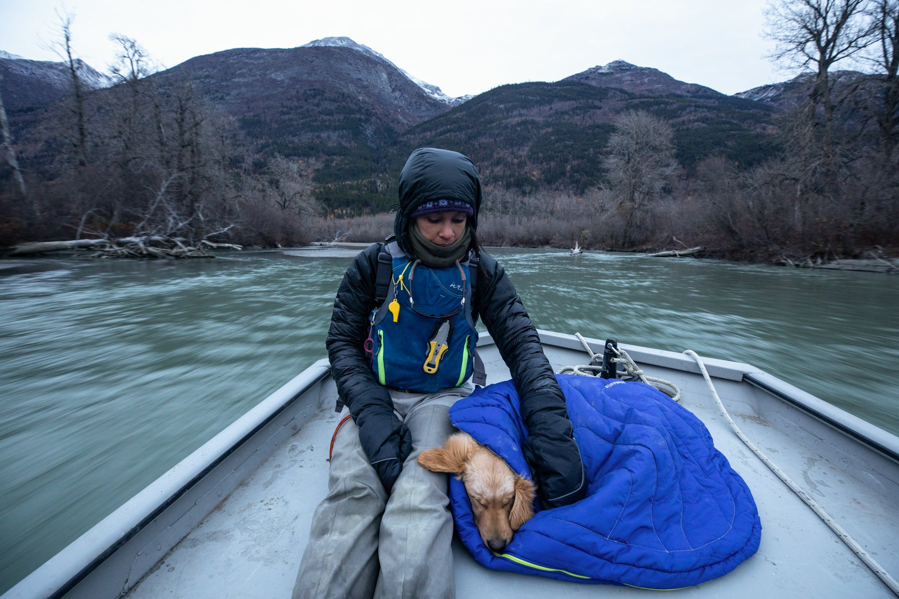 Sammy snuggles next to Chris on a highlands dog sleeping bag in the bow of the boat.