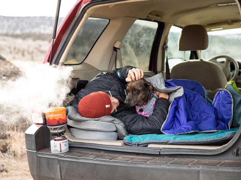 Trevor and Kahlua sleep in the back of the car while water boils on the jetboil.