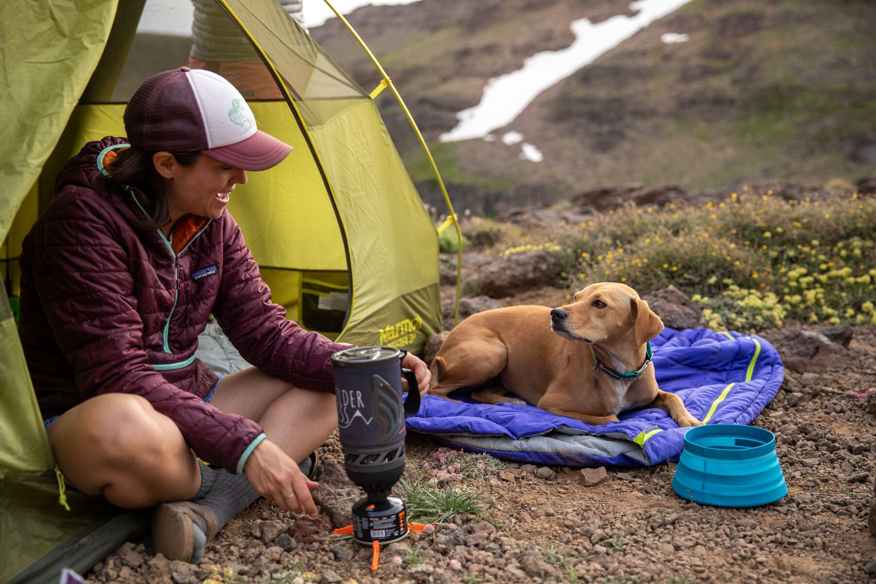 Human sitting in edge of tent cooking on her camp stove while dog sits next to her in Highlands dog sleeping bag.