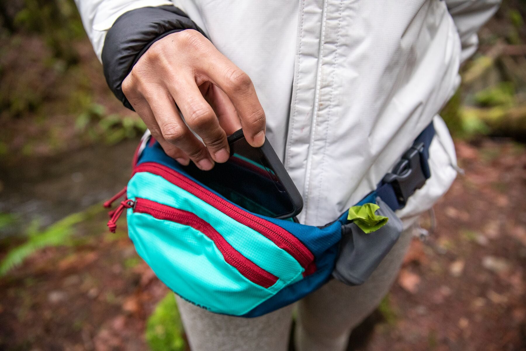 Human puts into phone pouch into home trail hip pack.