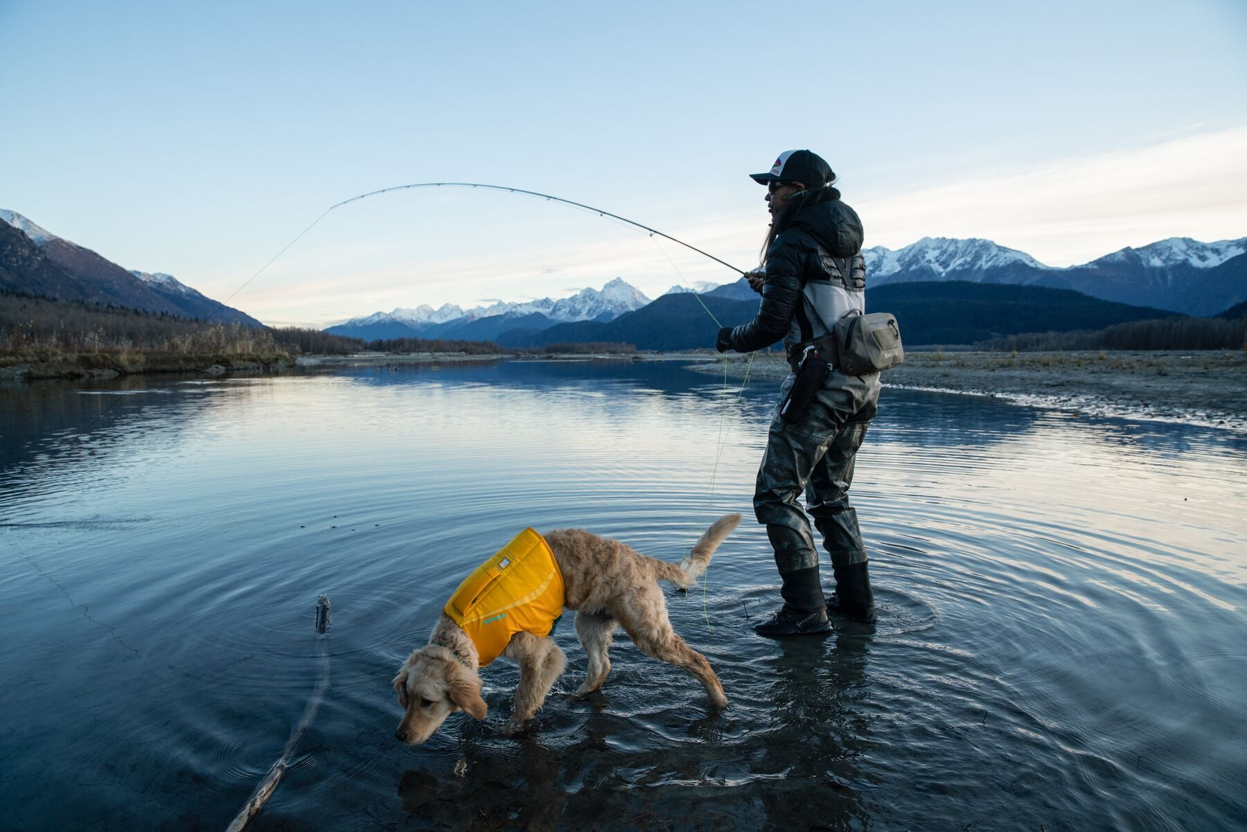 Woman fly fishing in river at base of Alaska mountains with puppy in float coat dog life jacket walking in water alongside her.