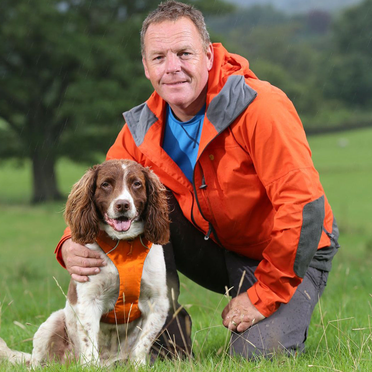Kerry poses on the trail with his dog in an orange front harness that matches his raincoat.
