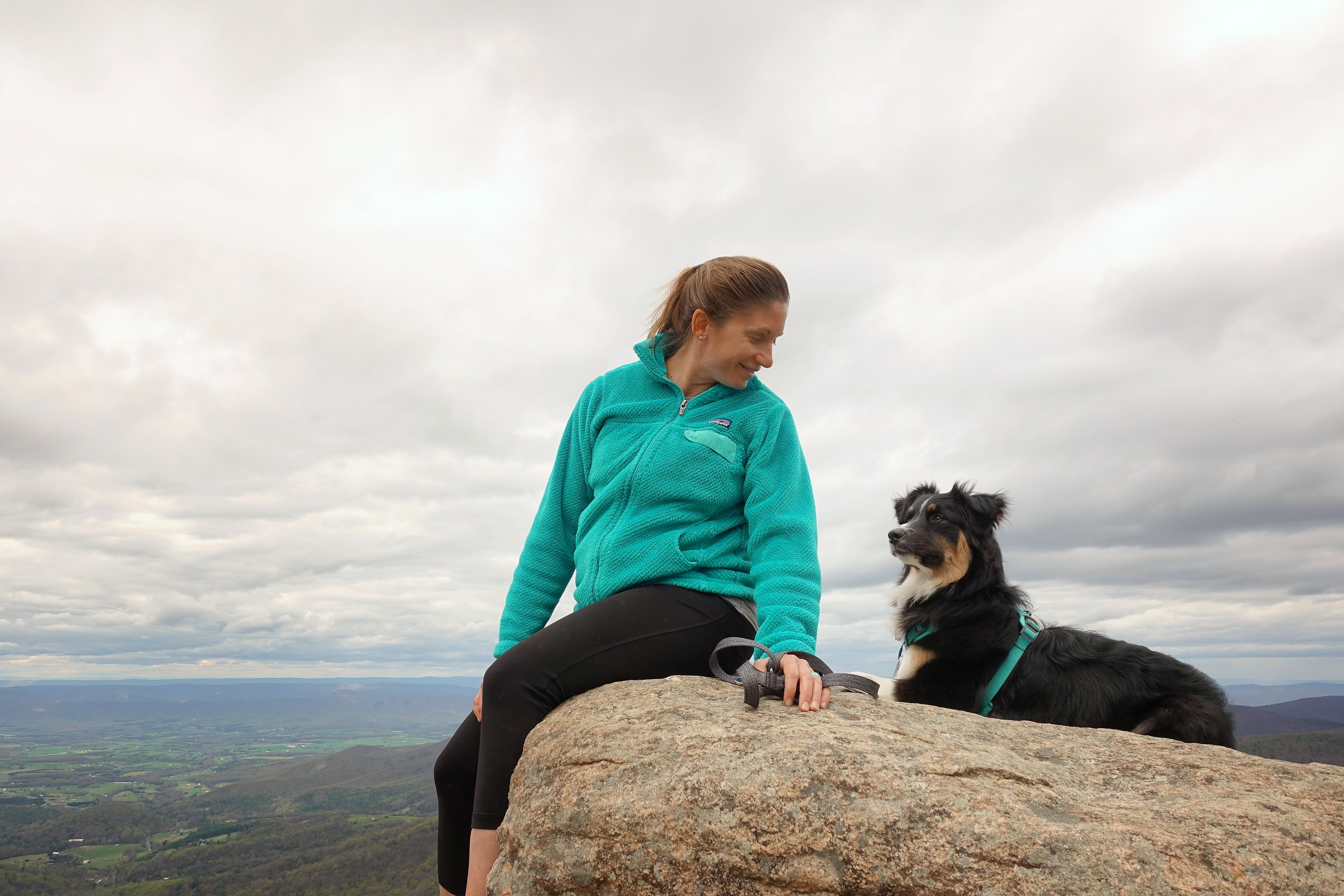 Maria and her pup sitting up on a viewpoint.