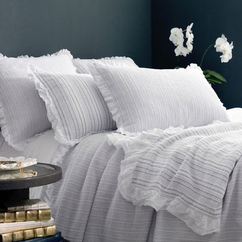 white matelasse coverlet with gray stripes on bed with pillows