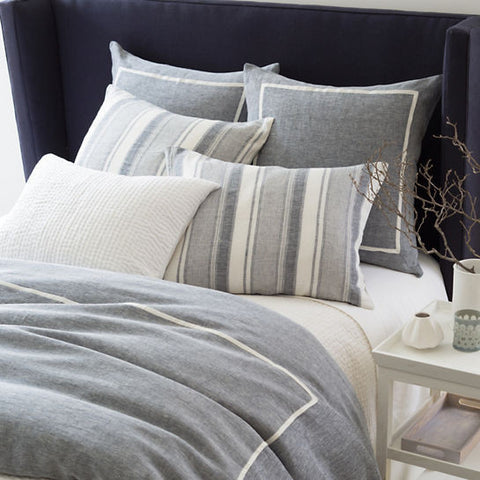 gray blue duvet on bed with white piping