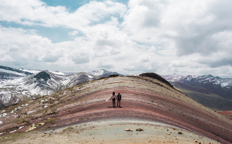 Couple walking on the alternative rainbow mountain palccoyo