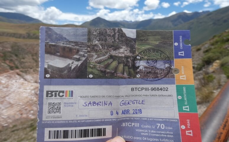 Holding partial tourist ticket Cusco in front of Maras salt mines