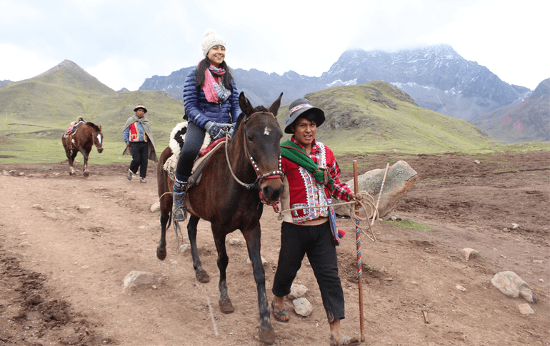Girl with horse and porter during Vinicunca Rainbow Mountain Trek