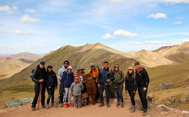 Travelers with an alpaca in front of the Rainbow Mountain Palccoyo