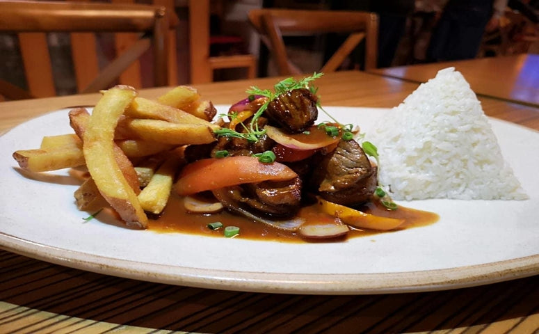 Lomo Saltado served on white plate