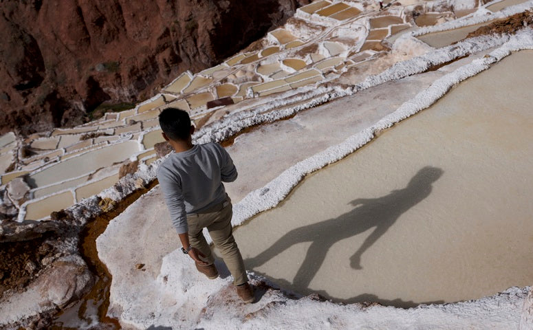 Traveler walking between Maras salt mines