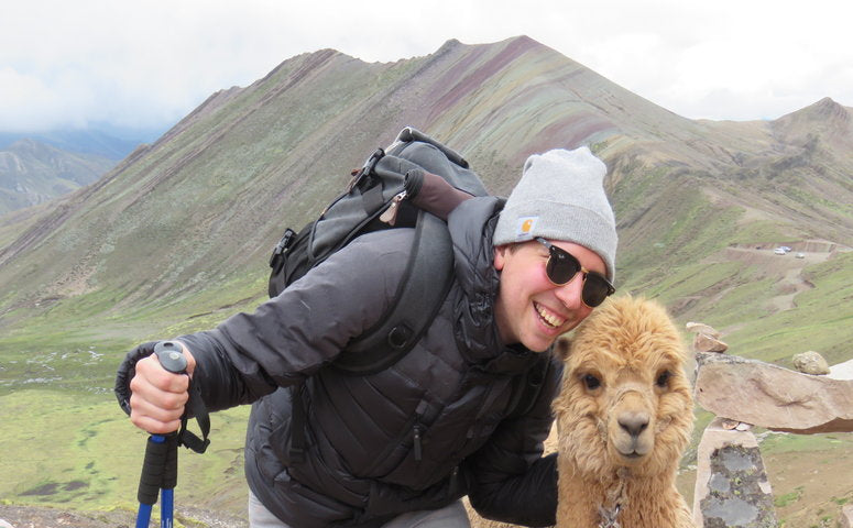 Guy taking a picture with holding an alpaca in his arm in front of Palccoyo rainbow mountain