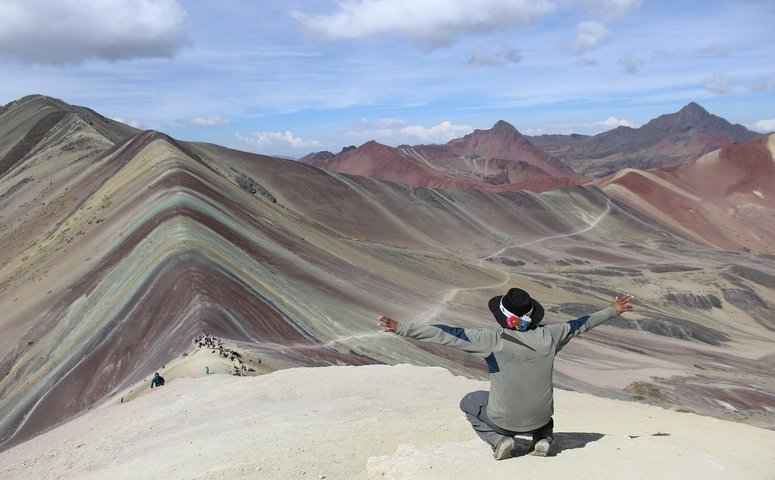 Vinicunca rainbow mountain and explorer is kneeling in front of it with arms in the air