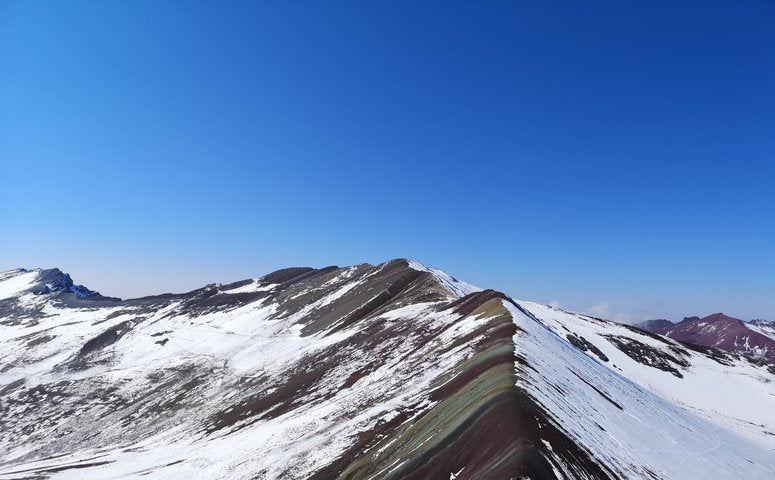 Snow-capped Vinicunca mountain with blue sky