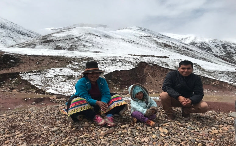 Explorer next to a child and women from the local community