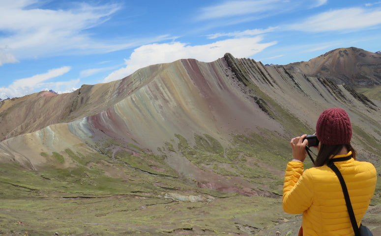 Explorer is taking a picture of the alternative Rainbow Mountain Palccoyo