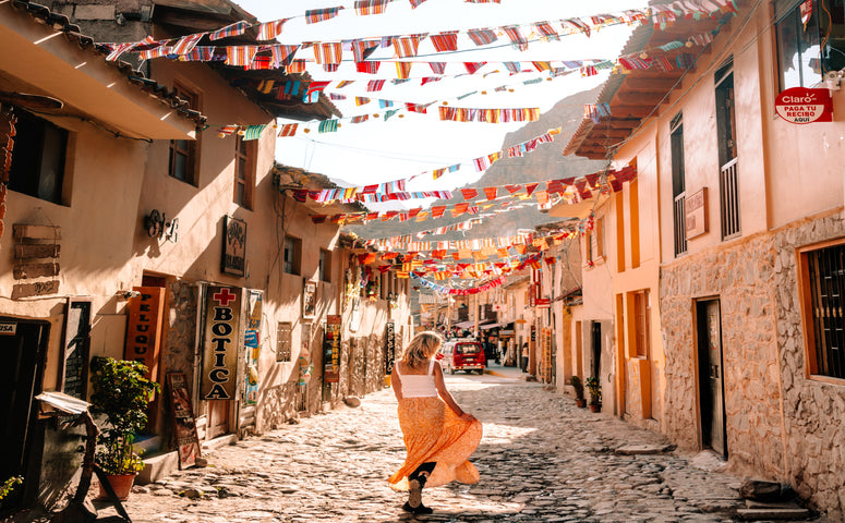 Girl in a orange skirt walking through the colorful streets