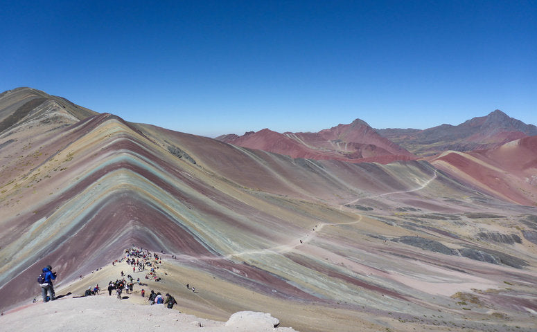 Rainbow mountain in different colors and some traveler in front of the pic