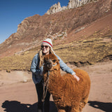 Girl with alpaca during rainbow mountain tour