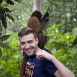 Man with monkey on his shoulders in Iquitos jungle