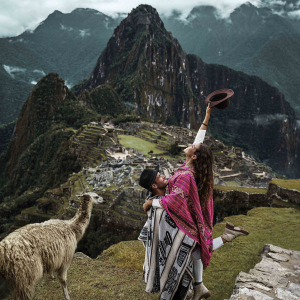Couple at Machu Picchu viewpoint with llama
