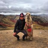 Traveler with llama at Rainbow Mountain Palccoyo