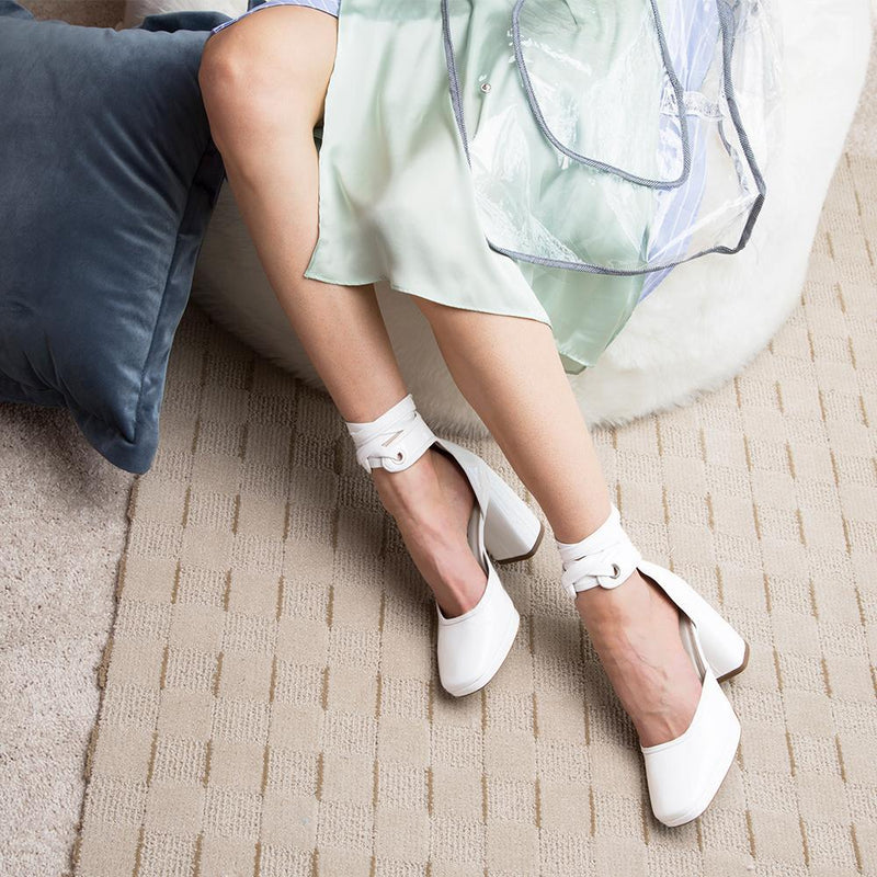 Woman Wearing Daniella Shevel Women's Square Toe Pump in White Leather with Leather Ankle Strap