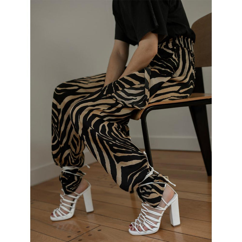 DANIELLA SHEVEL designer vegan shoes in white strappy sandals on model with black tshirt and pants
