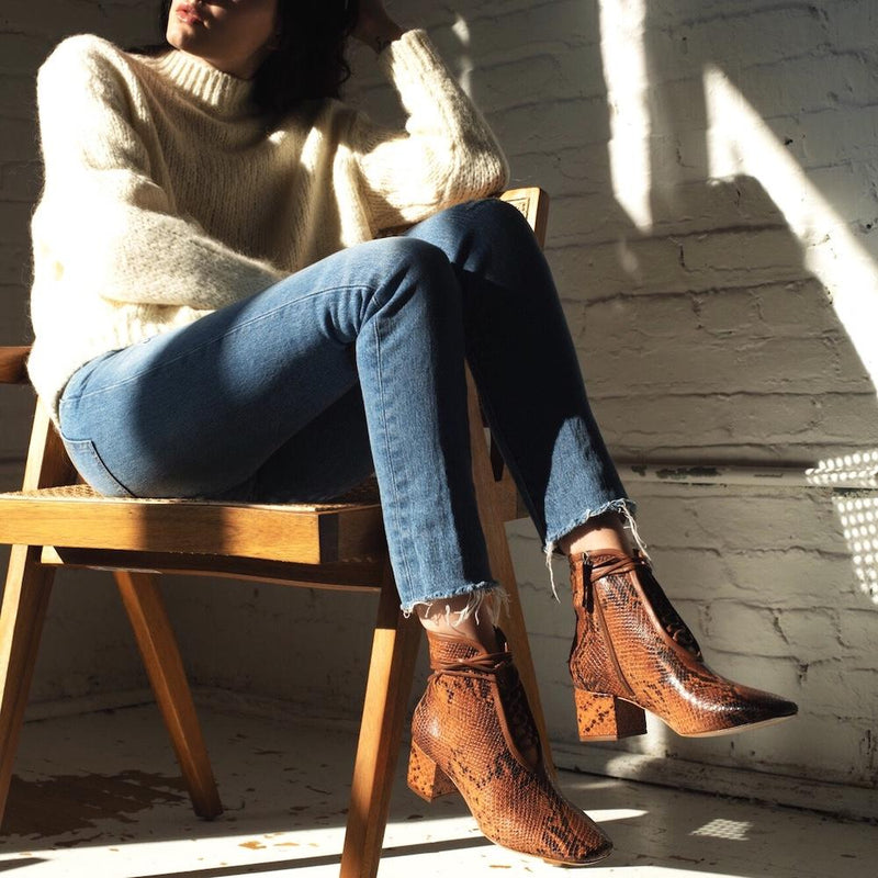 Daniella Shevel Cleo Brown Printed Snake Leather Boot with low Heel on model with denim jeans and cashmere sweater