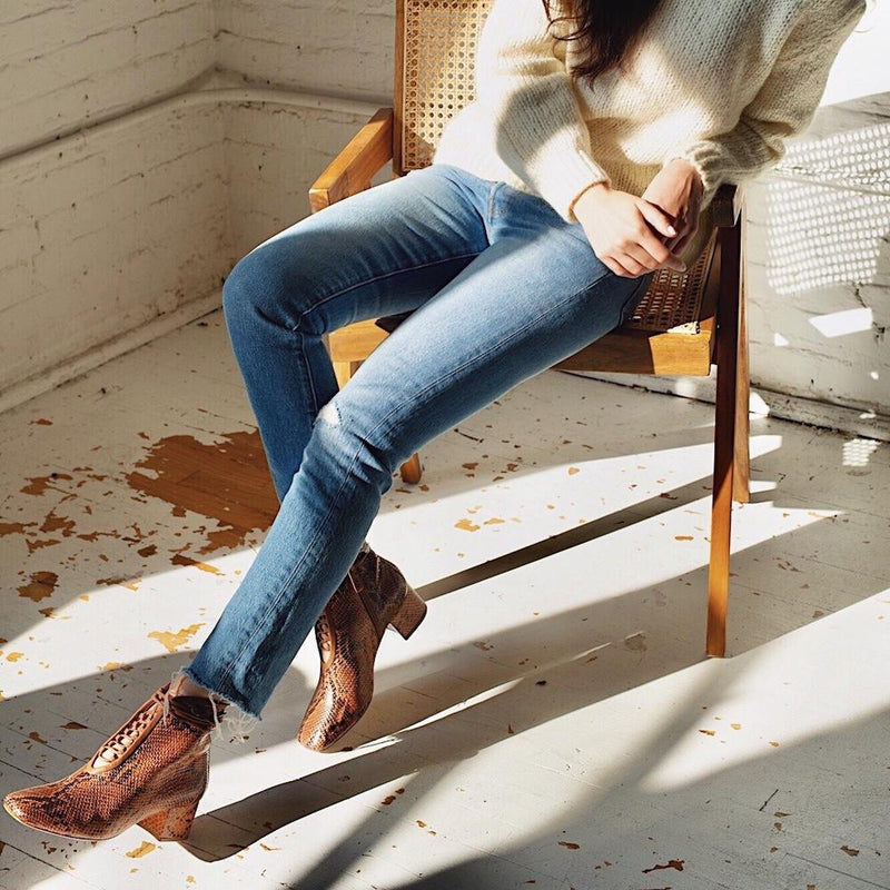 Daniella Shevel Cleo Brown Printed Snake Leather Boot with low Heel on model with denim jeans on chair