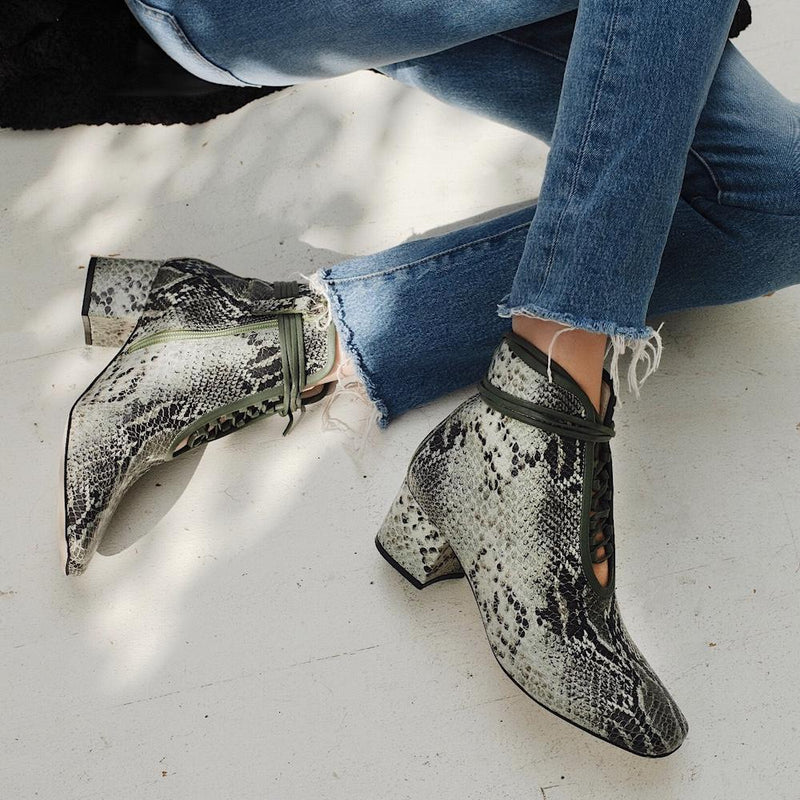 Daniella Shevel Cleo Green Printed Snake Leather Boot with low Heel on model with denim jeans on chair