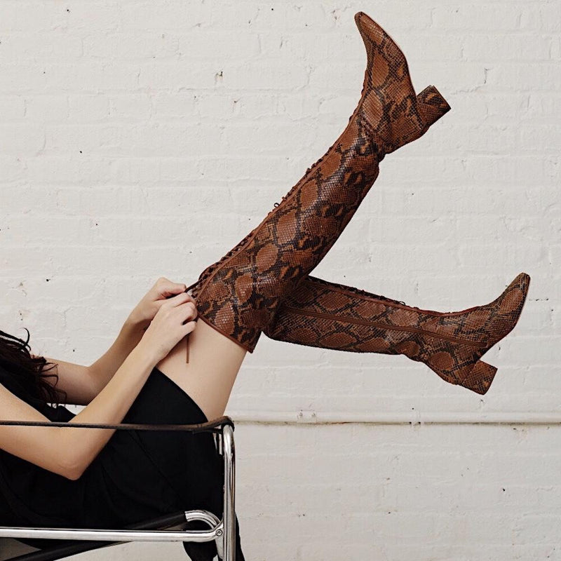 Daniella Shevel Koa Brown Printed Snake Leather Boot with low Heel over the knee on model with black dress on chair