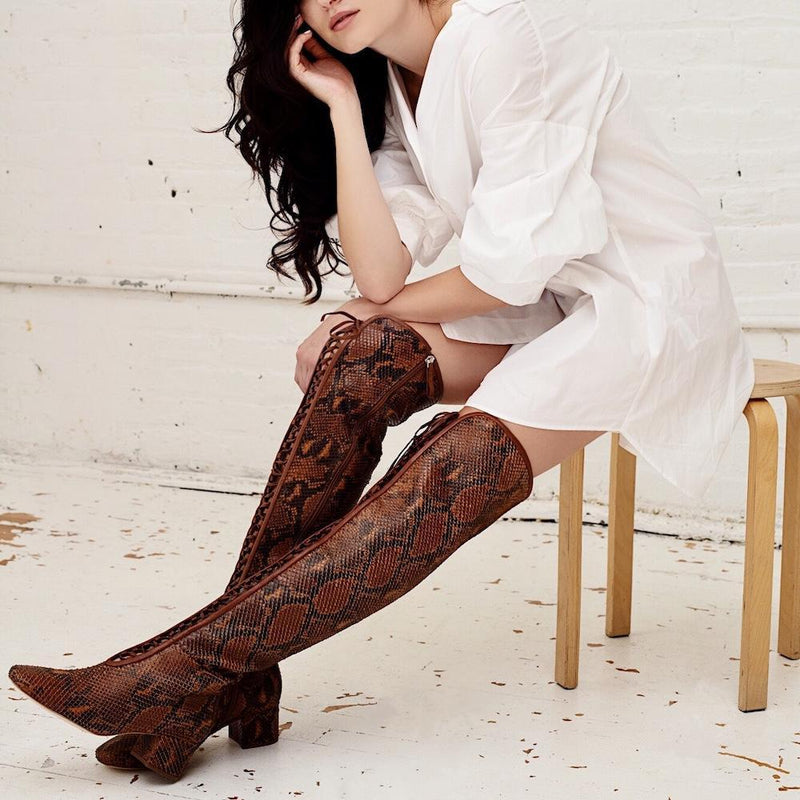 Daniella Shevel Koa Brown Printed Snake Leather Boot with low Heel over the knee on model with white shirt dress