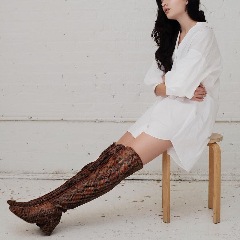 Daniella Shevel Koa Brown Printed Snake Leather Boot with low Heel over the knee on model with white shirt dress look