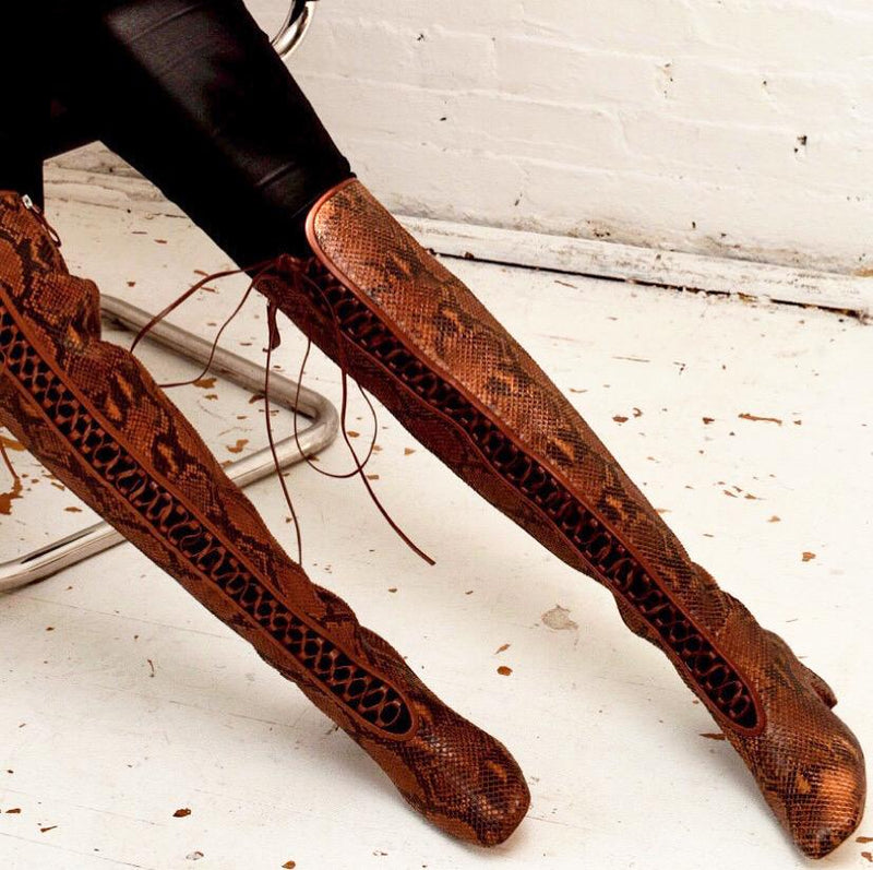 Daniella Shevel Koa Brown Printed Snake Leather Boot with low Heel over the knee on model with black jean pants