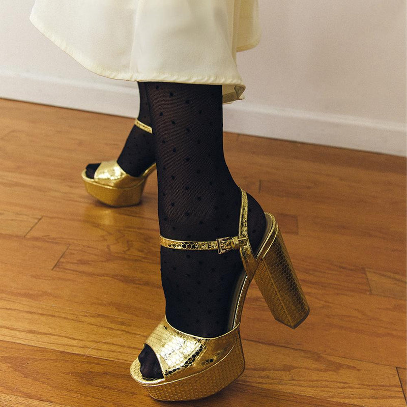 Daniella Shevel Vegan Gold Printed Crocodile Metallic Platform Heel Sandal On Model In A White Holiday Dress close up with tights