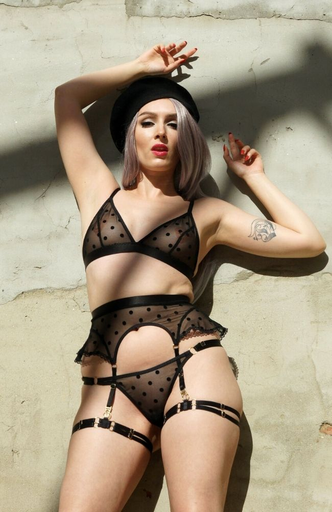 Estee suspender belt made from black mesh with flocked polkadots and lace ruffle trip. four suspender clips.
