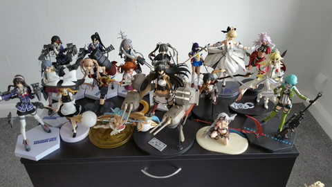 anime figures and anime collectables on a bedroom table