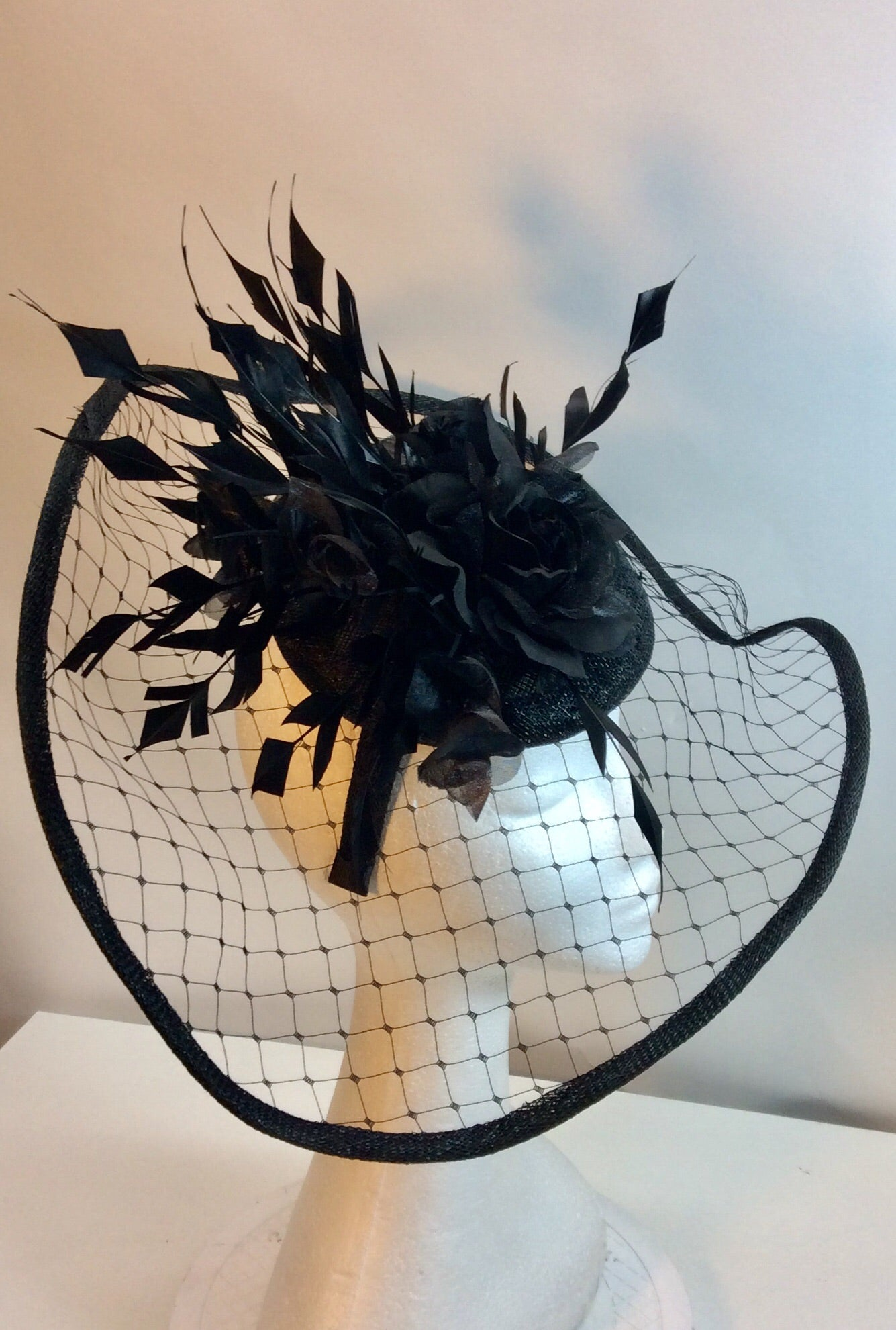 Fabulous black hat style fascinator with netting flower and feathers