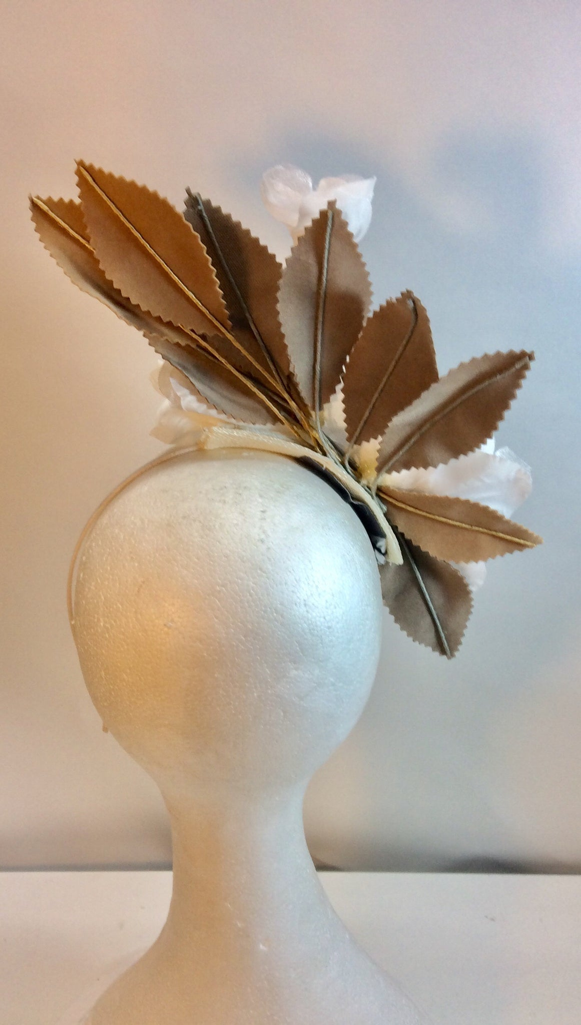White floral fascinator with taupe leaves