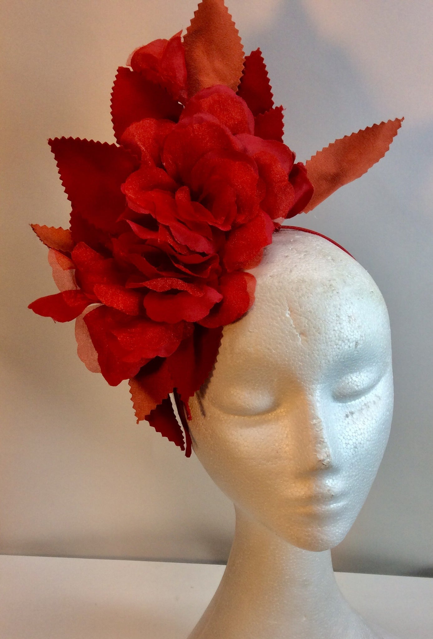 Coral red floral fascinator with serrated leaves