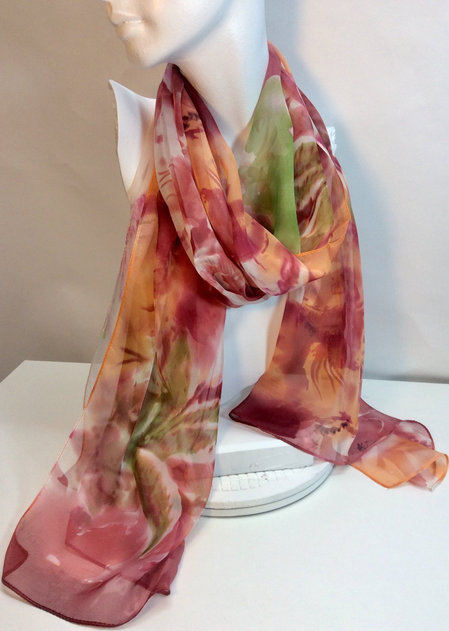 Muted tones of orange and green feature on this silk scarf